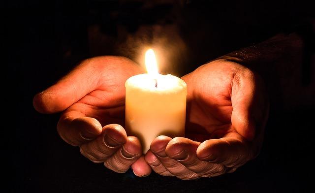 ruce nabízející světlo svíčky