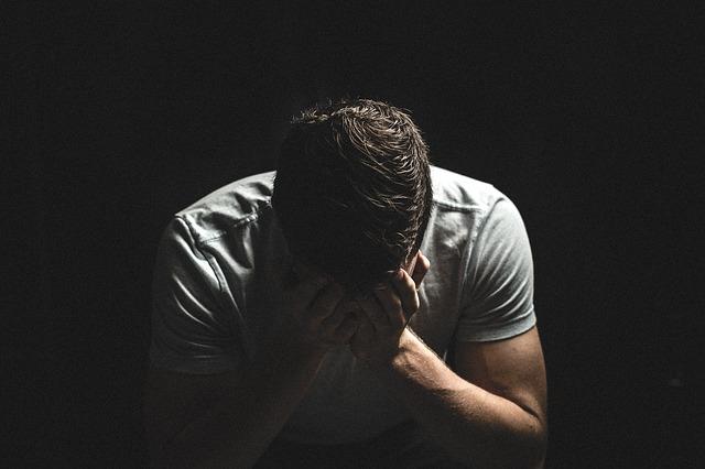 smutný muž sedící ve tmě