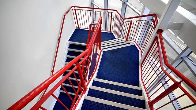 schodiště s modrým kobercem a červeným kovovým zábradlím