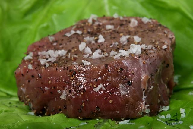Hovězí syrový steak, posypaný pepřem a solí