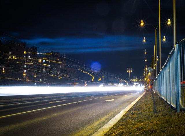 silnice v noci, projíždějící světla, plot a město