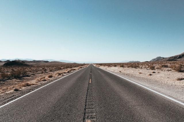 silnice v poušti, opuštěná vozovka kolem písčité pláně