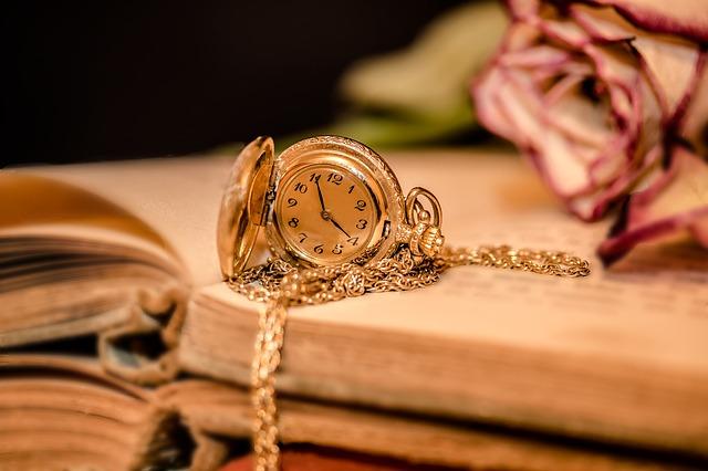 kapesní hodinky na knize s květinami