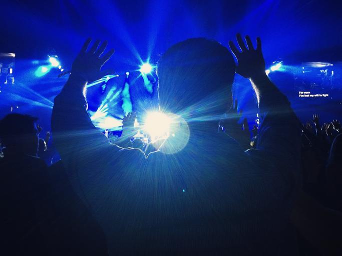 párty, modrá světla, kluk co zvedá ruce vzhůru, mnoho lidí
