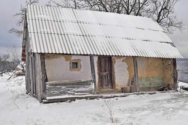starý domeček, otlučená žlutá omítka, stojí v zimě zasněžený.jpg